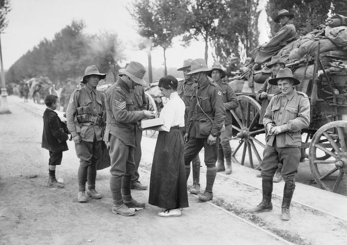 black and white photo of woman selling chocolates to soldiers