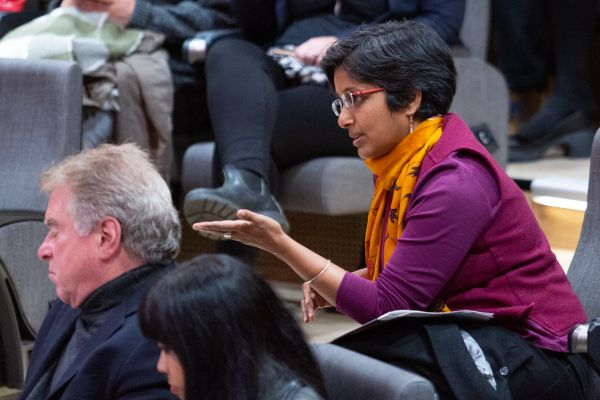 A staff member in the audience asks a question at the evening lecture