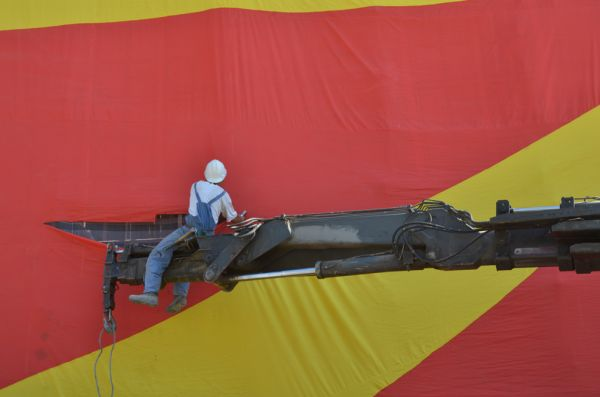 A construction worker repairing a Macedonian-flag coloured scaffolding net without protection harness.