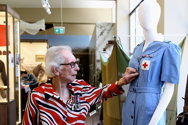 Woman wearing medals with a Nurse's uniform on a mannequin