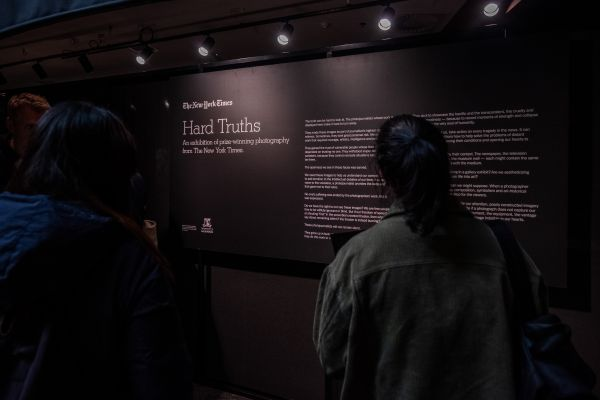 A student reads the Hard Truths exhibition signage