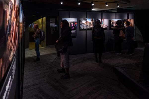 Silhouetted students view images in the exhibition