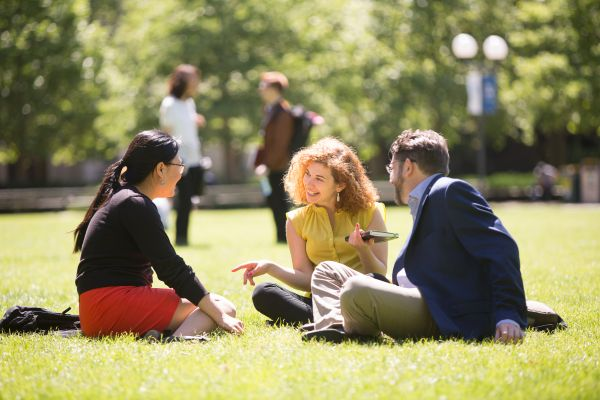 Three students sitting on the grass during a sunny day on the South Lawn