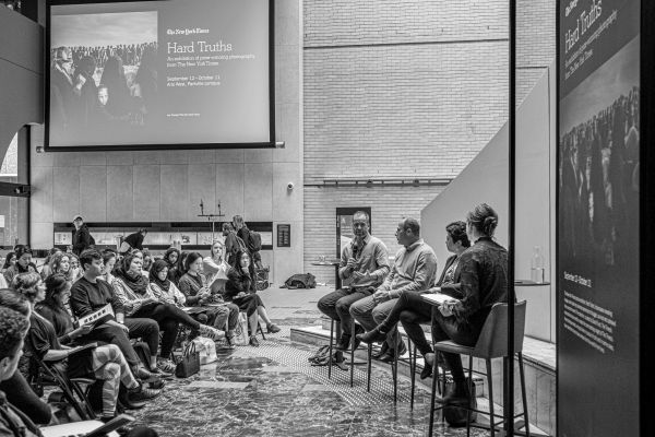 Black and white photo of the panelists and emcee at the Q&A event