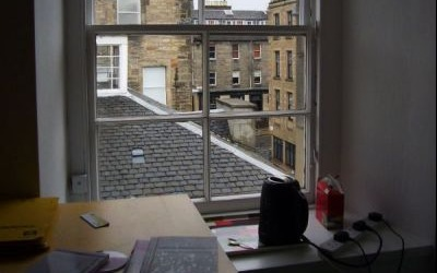 A view from a home study looking out of a window to rooftops beyond