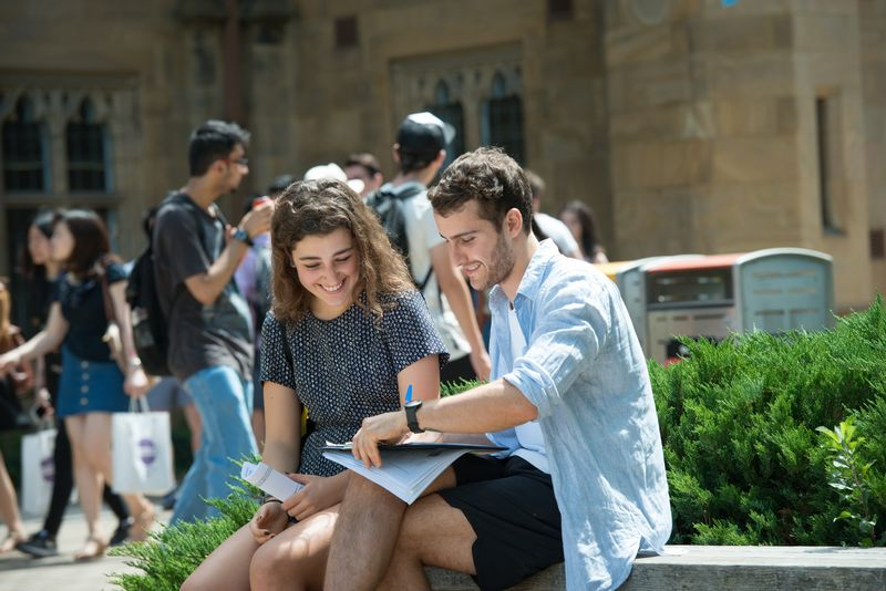 a male and female student sitting outside on a university campus