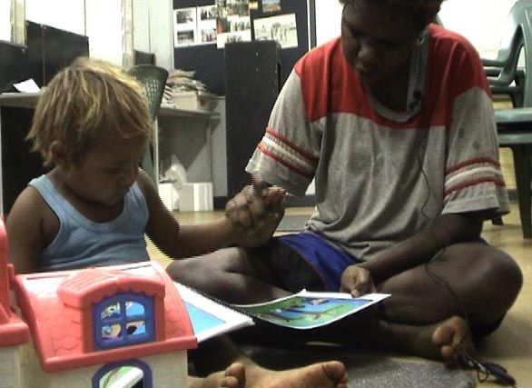 Samantha Smiler Nangala-Nanaku telling a story to her son based on a picture-prompt book