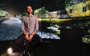 Professor Keir Winesmith sitting on a stool surrounded by projection displays