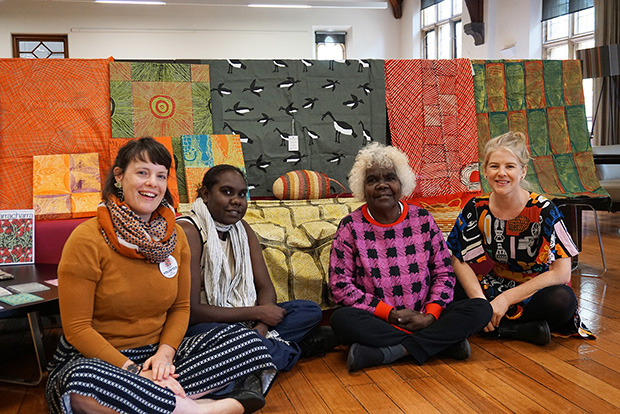 Four women sitting in front of tapestry