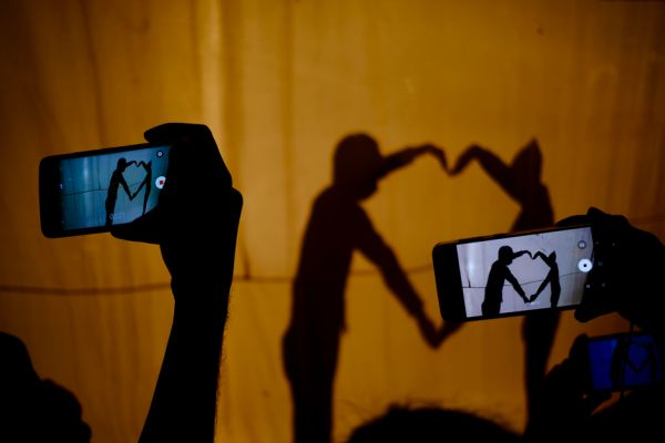 Family members video a shadow performance at a school in Lucknow, India.