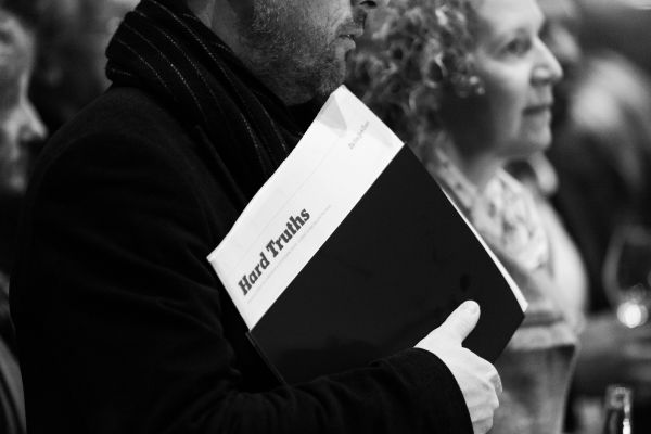 A man at the evening launch holds a printed program