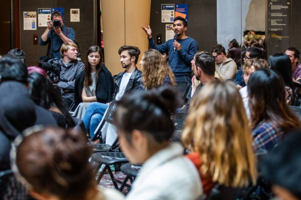 A student audience member stands to ask a question during the Q&A