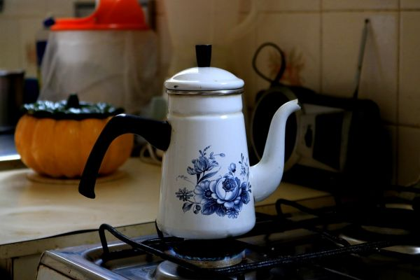 A photo of a small enamel teapot on a stove with blue flowers on it
