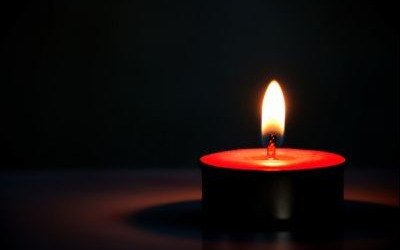 A picture of a small tealight candle in the darkness
