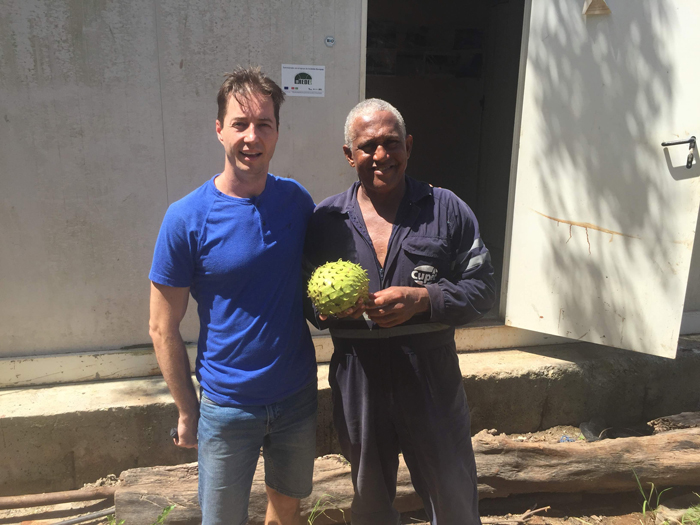 Two men looking at the camera, holding a piece of fruit